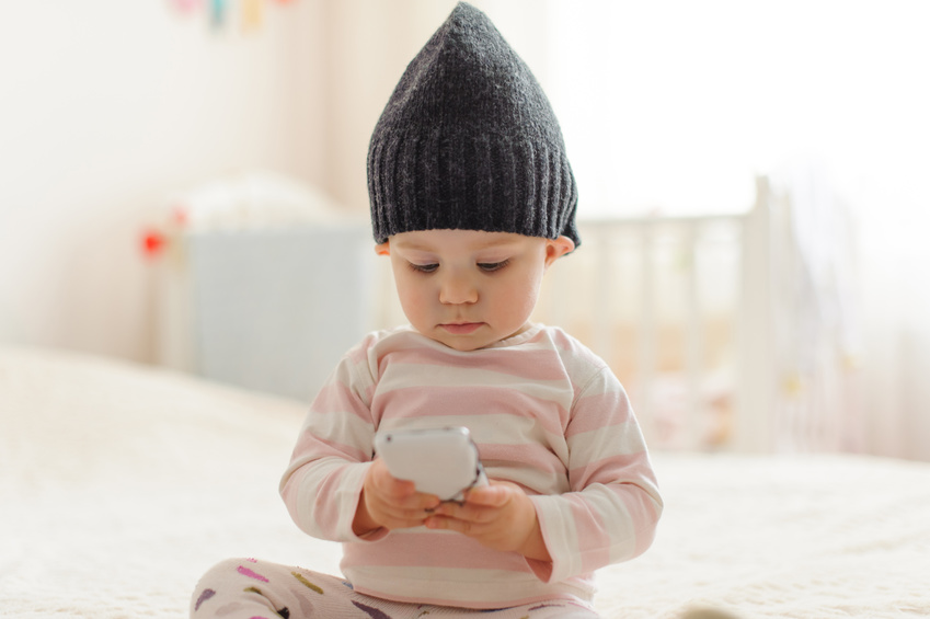 A Baby Playing with a Baby Monitor